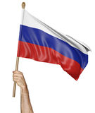 Hand proudly waving the national flag of Russia. Isolated on a white background Stock Photo