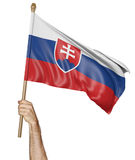 Hand proudly waving the national flag of Slovakia. Rendered in 3D and on a white background royalty free stock image
