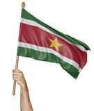 Hand proudly waving the national flag of Suriname Royalty Free Stock Photos
