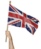Hand proudly waving the national flag of United Kingdom Stock Images