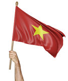Hand proudly waving the national flag of Vietnam. Rendered in 3D and isolated on a white background Stock Images