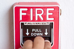 Hand pull down fire alarm switch. On factory wall Stock Photo