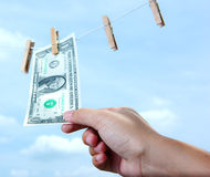 Hand pull money from clothes line. Pulling money from clothes line in monetary concept royalty free stock photos
