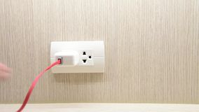Hand pull out charger adapter unplugging it in a typical electrical outlet stock footage