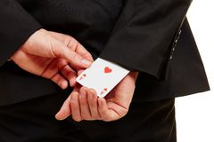 Hand pulling an ace from a sleeve. Hand from a businessman pulling an ace from a sleeve Stock Photography