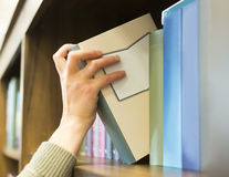 Hand pulling a book off the shelf Stock Photo