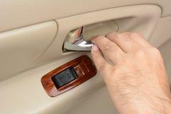 Hand pulling car interior door handle, opening the door Stock Image