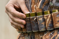 Hand pulling cartridge from the bandoleer Royalty Free Stock Image