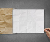 Hand pulling crumpled paper from recycle envelope Stock Photos