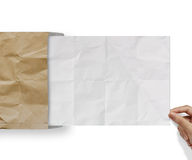 Hand pulling crumpled paper from recycle envelope Stock Photo