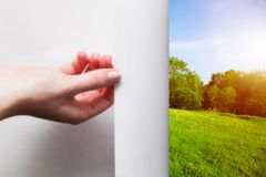 Hand pulling edge of a paper to uncover green landscape. Hand pulling edge of a paper to uncover, reveal green landscape. Page curl, conceptual Royalty Free Stock Images