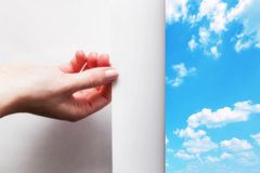Hand pulling edge of a paper to uncover, reveal blue sky. Hand pulling edge of a paper to uncover, reveal sunny blue sky. Page curl, conceptual Royalty Free Stock Images