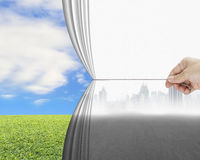 Hand pulling gray cityscape curtain discovered natural sky meado Royalty Free Stock Photos