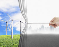 Hand pulling gray cityscape curtain revealing group of wind turb Stock Photo