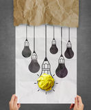 Hand pulling light bulb crumpled paper out of recycle envelope Royalty Free Stock Image