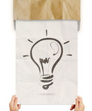 Hand pulling light bulb crumpled paperfrom recycle envelope royalty free stock photos
