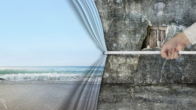 Hand pulling natural sandy beach curtain covered old broken wall Royalty Free Stock Image