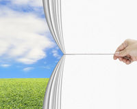 Hand pulling open white blank curtain discovered natural sky mea Stock Images