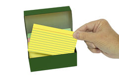 Hand Pulling Out Brightly Colored Index Card From Box. Male hand pulling a bright yellow colored index card from vintage metal box and shot on a white background Royalty Free Stock Photography