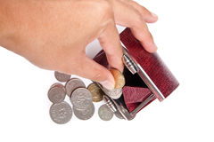 Hand pulling out coins from red purse Stock Image