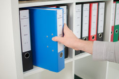 Hand pulling out a folder from a shelf Stock Photo