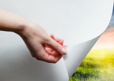 Hand pulling a paper corner to uncover, reveal green landscape stock photos