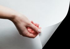 Hand pulling a paper corner to uncover, reveal something. Hand pulling a bottom paper corner to uncover, reveal something. Page curl, conceptual Stock Photography