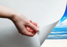 Hand pulling a paper corner to uncover sunny beach Royalty Free Stock Photography