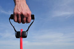 Hand Pulling a Resistance Band. Against a Blue Sky Royalty Free Stock Photography