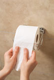 Hand pulling toilet paper roll in holder Stock Image