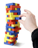 Hand Pulls Block from Tower Stock Image