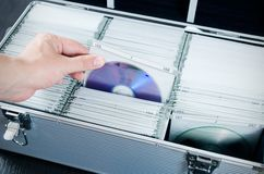 Hand pulls disc from CD-DVD case Stock Photo