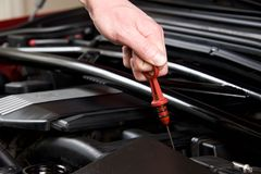 Hand pulls out oil dipstick in a clean car engine bay. Close up of a hand pulling out oil dipstick in a clean car engine bay Stock Images