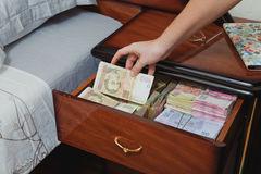 Hand pulls out wad of money from the bedside table Royalty Free Stock Photos