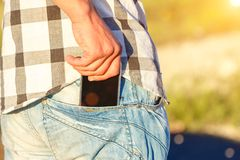 Hand pulls the phone out of his jeans pocket.  Royalty Free Stock Photography