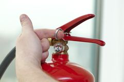 Hand pulls the pin from the extinguisher Stock Images
