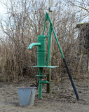 Hand pump leading to an artesian well. Royalty Free Stock Photo