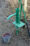 Hand pump leading to an artesian well. Stock Photo