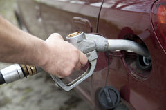 Hand pumping gas in the car with a gas pump Royalty Free Stock Images