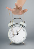 Hand puppeteer manipulating clock, time management concept. Hand puppeteer manipulating alarm clock, time management concept Royalty Free Stock Photo