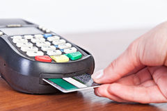 Hand push credit card Into a credit card machine. Royalty Free Stock Photo