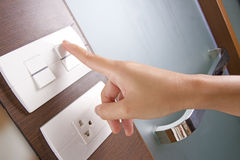 Hand push switch. Female hand pushing white electricity switch on the wall Stock Images