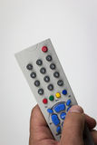 Hand pushes button on dusty, old, simple TV remote Stock Image