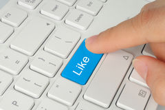 Hand pushing blue like button. On keyboard close-up stock photography