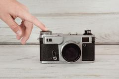 Hand pushing the button of a retro film camera on grey background. Hand pushing the button of a retro film camera on grey wooden background stock image