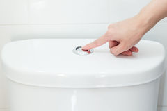 Hand pushing a button to flush Stock Photo