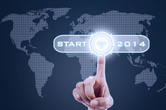 Hand pushing a button. Of 2014 on world map screen Stock Photography