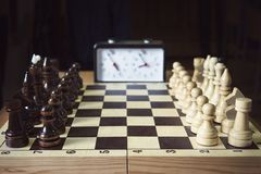 Hand pushing chess time clock. Playing quick chess with timer on dark background stock images