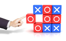 Hand pushing a circle to win the tic tac toe game Stock Photo