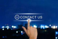 Hand pushing contact us button on touch screen. Hand clicking contact us button on a touch screen interface Royalty Free Stock Images
